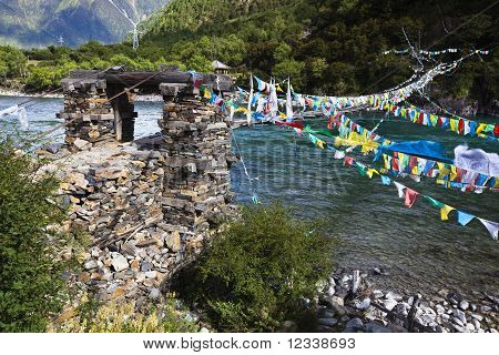 tibet: rope bridge with prayer flags