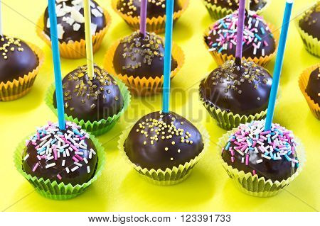 Chocolate cake pops with sticks over yellow background