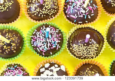 Chocolate cake pops on yellow for background