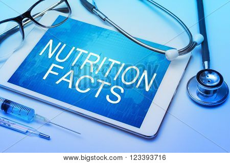 Nutrition Facts word on tablet screen with medical equipment on background