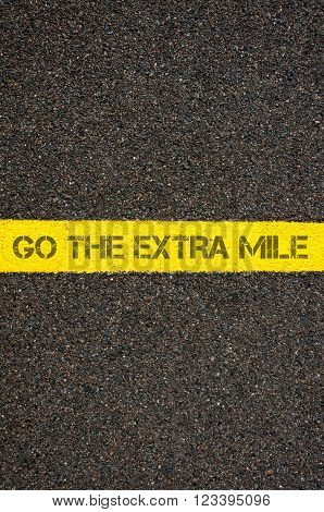 Road marking yellow paint dividing line with words GO THE EXTRA MILE, concept image