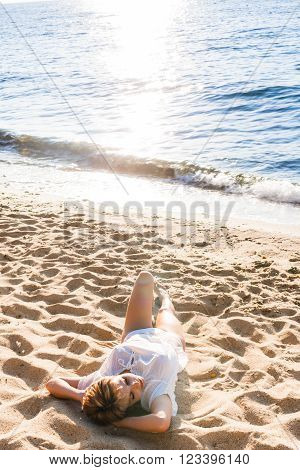 Happy woman resting on sand near by water
