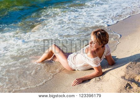 lovely woman in white blouse lying on the sea beach