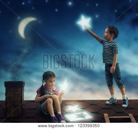 Fairy tale! The children hung the stars in the sky. Boy and girl on the roof cut out stars.