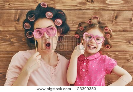 Funny family! Mother and her child daughter girl with a paper accessories. Beauty funny girl holding paper glasses on stick. Beautiful young woman holding paper glasses on stick.