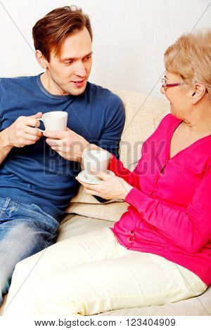 Mother and son sitting on couch and drinking tea or coffee