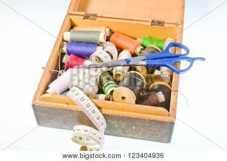 small box with sewing belonging  on a white background