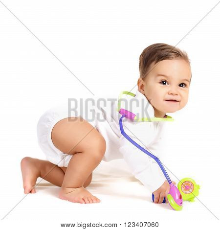 Portrait of a curious little boy,brunette with brown eyes and short hair,dressed in a white shirt and a white diaper,barefoot posing in Studio,sitting on a white background, smiling mouth open,plays with a toy stethoscope