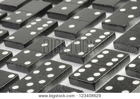 Composition of lying black domino bricks with white dots