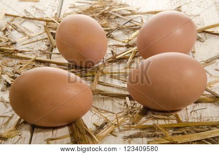 free range brown eggs with straw on an old white wooden table