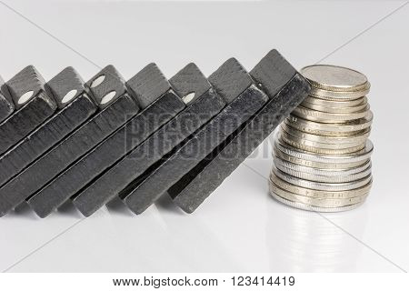 Conceptual composition of falling black domino stones as a continuous process and a pile of coins which disrupt this main process