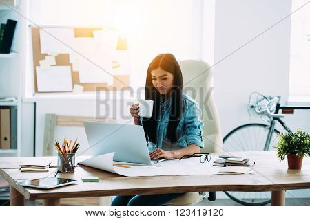 Casual working day of modern architect. Beautiful young Asian woman using laptop and holding coffee cup while sitting at her working place