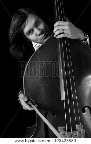 Melancholy musician with a contrabass over black background. bnw