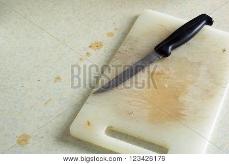 Dirty kitchen food preparation chopping board and knife.