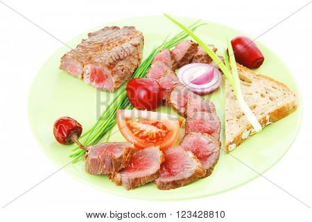 main course : roast red meat slices served on green plate with tomatoes and sprouts isolated on white background