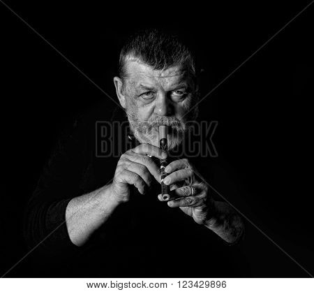 Black and white portrait of old musician playing Ukrainian woodwind instrument sopilka