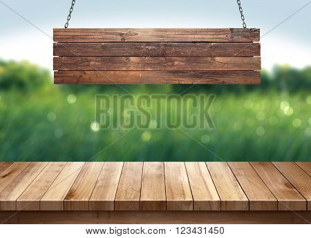 Wood table with hanging wooden sign on green nature blurred background