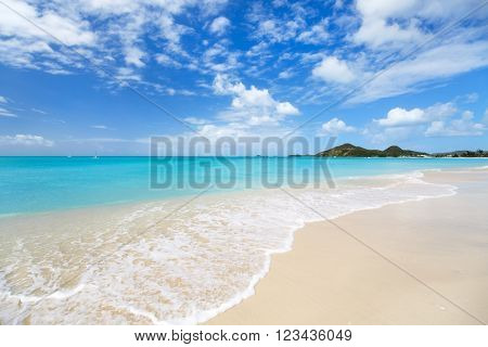 Idyllic tropical beach with white sand, turquoise ocean water and blue sky at Antigua island in Caribbean poster