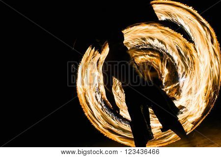 a man showing fire dancing flaming trails.