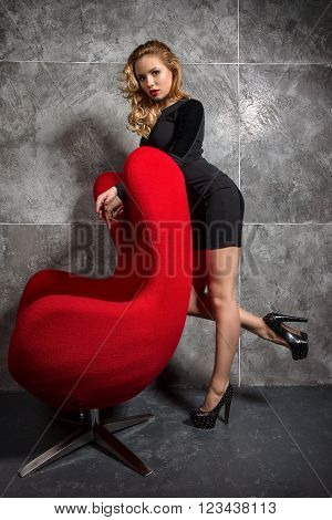 Beautiful blonde in a black slinky dress and shoes with high heels posing standing near red armchair.
