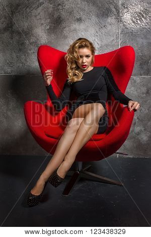 Beautiful blonde girl in a black slinky dress and black shoes sitting in the red chair. girl in an easy relaxed position sits in the chair.