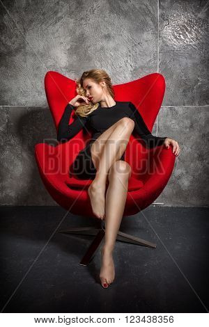 Beautiful blonde girl in a black slinky dress sitting in the red chair. girl in an easy relaxed position sits in the chair.