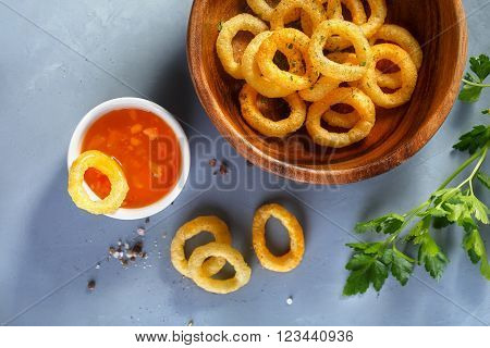 Fried onion rings  in batter with sauce. Food background, Top view