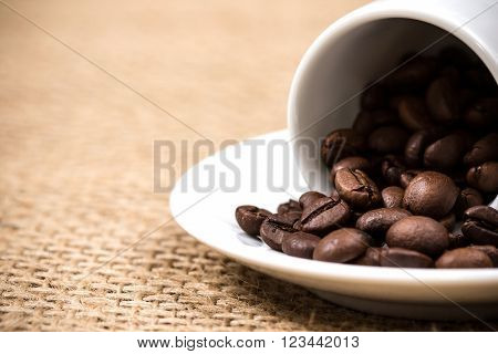 White coffeecup and plate with spilled coffeebeans on gunny background