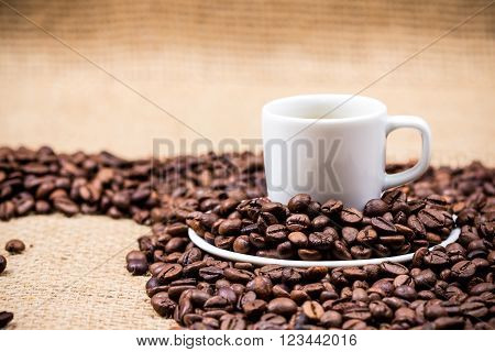 White coffeecup and plate on coffeebeans on gunny background
