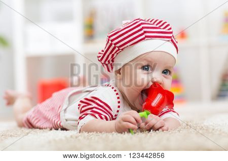 Baby hold a toy lying on belly in the  nursery