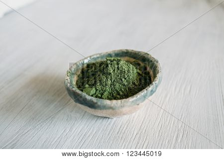 ceramic bowl with a green pigment basma green on a white background green pigment
