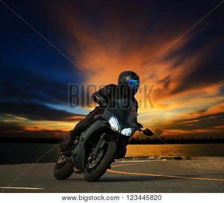 young man riding big bike motorcycle leaning curve on asphalt highways road against beautiful dusky sky use as people adventure sport leisure theme