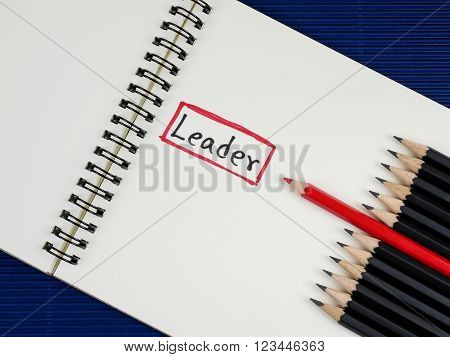 Red pencil standout from black pencil and handwriting word Leader on blank notebook with blue corrugate paper background leadership business concept poster