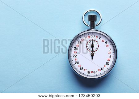 Stopwatch on blue background, close up