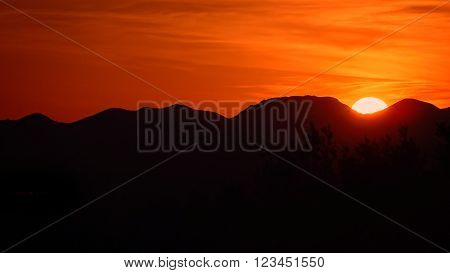 Sunset behind Sonoran Desert mountains in Saguaro National Park