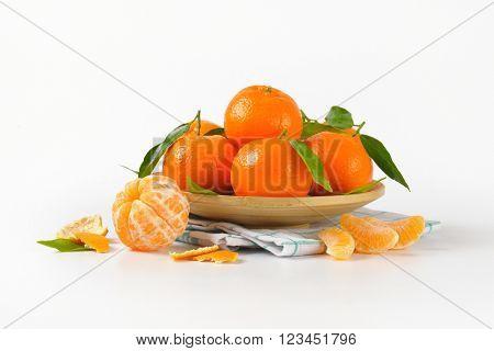 plate of ripe tangerines on checkered dishtowel
