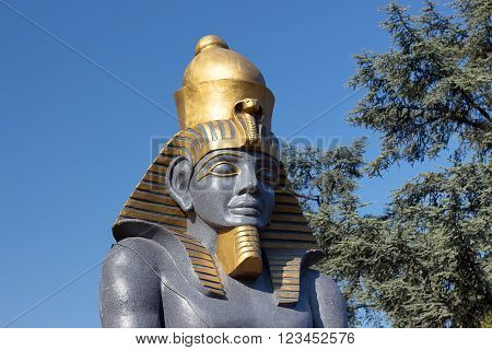 Statue of Pharaoh against a background of blue sky and trees. Decorative sculptures with Egyptian motives.