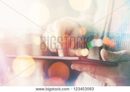 Man using digital tablet computer casual ordinary adult caucasian man with wireless gadget browsing internet multilayered double exposure image selective focus with very shallow depth of field.