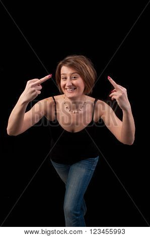Attractive young woman making obscene hand gesture showing middle fingers over black background