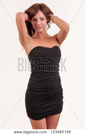 alluring woman in black dress posing on white