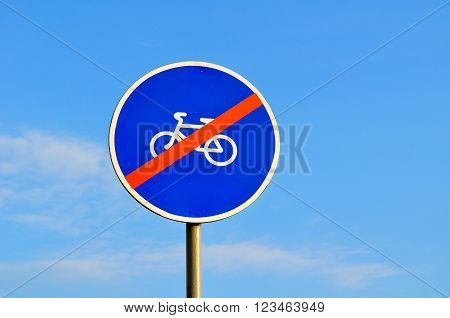 No cyclists road sign - closeup on background of the blue sky. This sign indicates that bicycles and tricycles are prohibited from passing beyond the sign.