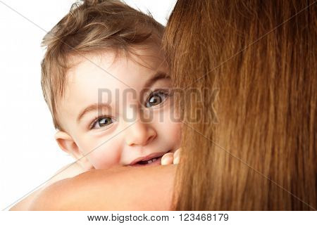 Baby boy playing peek-a-boo, cute little child looks out of his mother's shoulder, isolated on white background, happy family having fun
