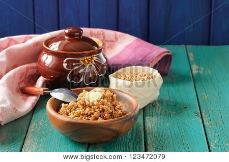 Boiled wholegrain spelt with butter in wooden bowl and raw spelt in linen bag on wooden table
