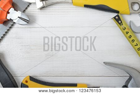 Top view of construction instruments and tools on wooden DIY workbench. Tape measure, wrench, hammer, pilers, screwdriver. Flat lay. poster