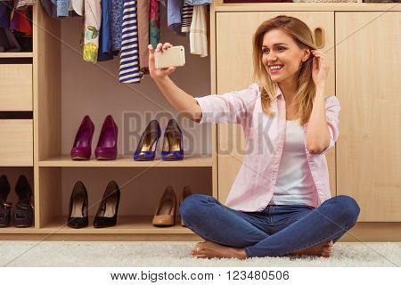 Beautiful girl is smiling and making a selfie using a smart phone sitting in her dressing room