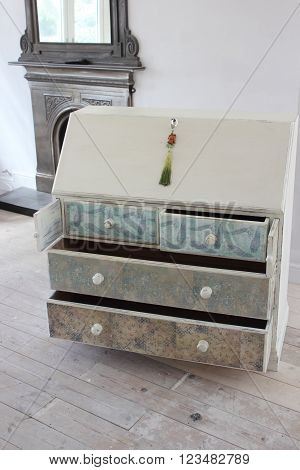 A finished and distressed bureau in an artists studio