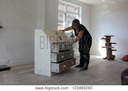 An artist painting and distressing a bureau in her studio, 2016