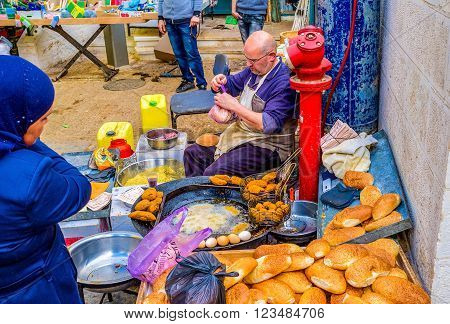 BETHLEHEM, PALESTINE - FEBRUARY 18, 2016: The outdoor cook prepares the falafel on frying pan in the Bethlehem market on February 18 in Bethlehem.