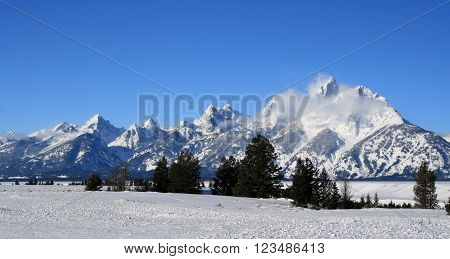 Snowmist blowing off Grand Tetons peaks in front of snowfield