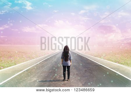 Back or rare of women standing on pavement road with dreamy morning sunlight, flower field  and lensflare background with copy space, concept road to heaven poster